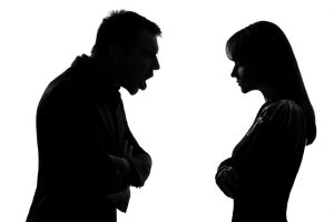 one caucasian couple man and woman face to face screaming shouting dipute in studio silhouette on white background